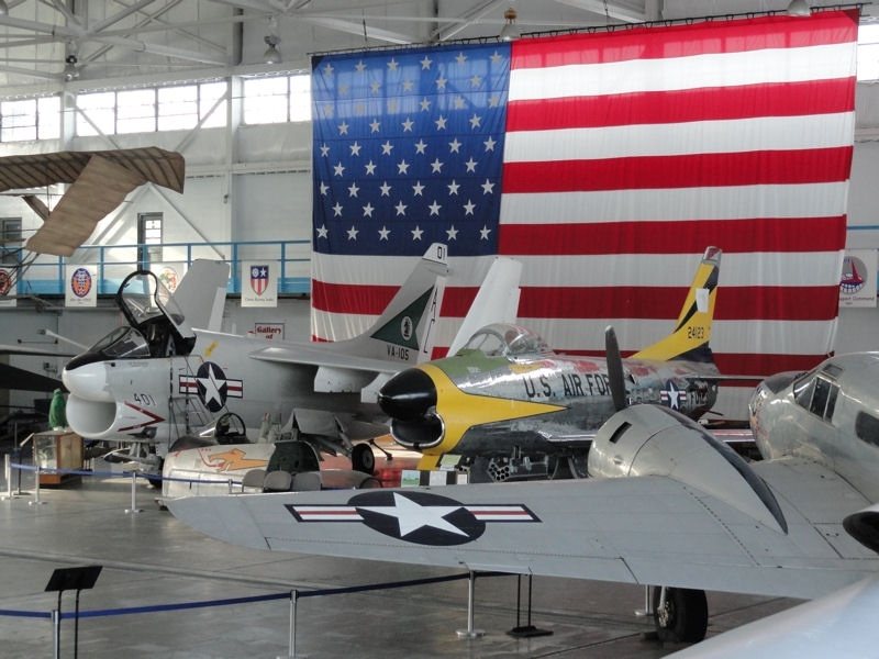 Picture of the Main Hanger at MAPS Air Museum. Pictured here are two aircraft that were restored by MAPS Members. The aircraft on the left is an A7E Corsair II and the aircraft on the right is an F-86 SabreDog.
