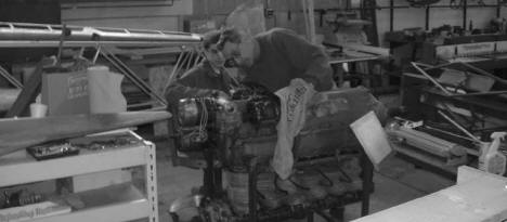 MAPS Member Jerry Saunders works on the PT-19 engine with a young volunteer. photo © Jim Kohan